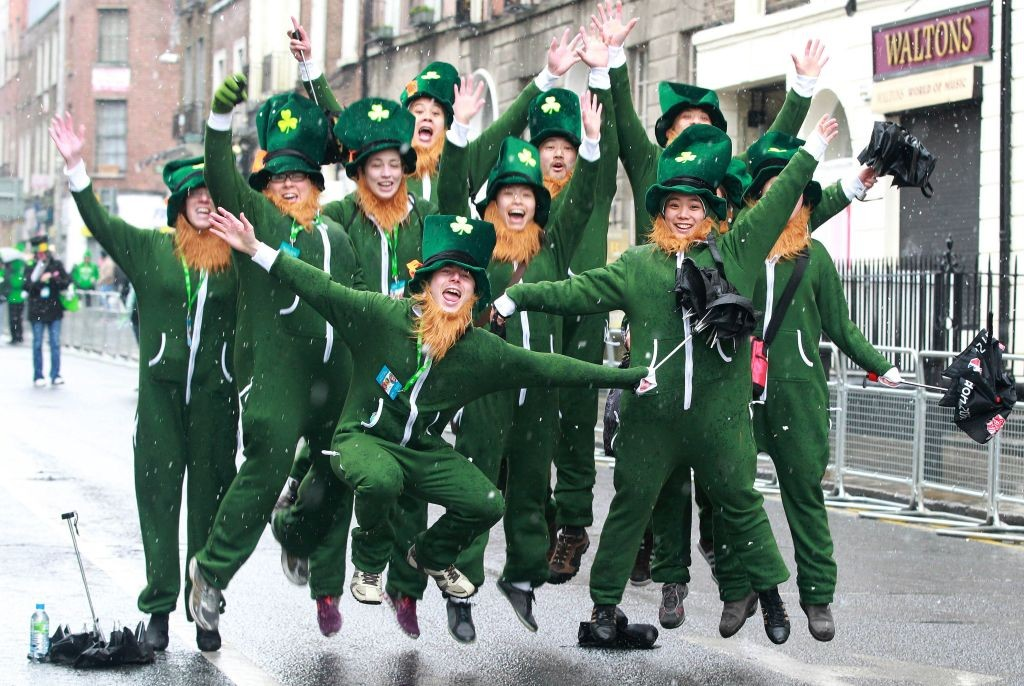 Parade goers dressed as leprechauns jump